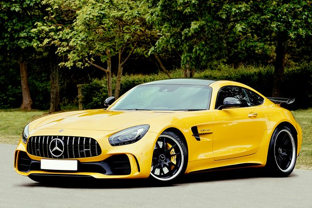 yellow mercedes benz beside trees in the road